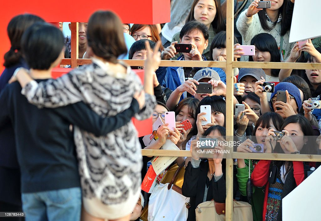 Fans take picture sof South Korean actresses Nam Ji-Hyun and Song Hye-Kyo and director Lee Jeong-Hyang at the greeting event for the film 'A Reason to live' during the Busan International Film Festival (BIFF) on October 8, 2011 AFP PHOTO / KIM JAE-HWAN