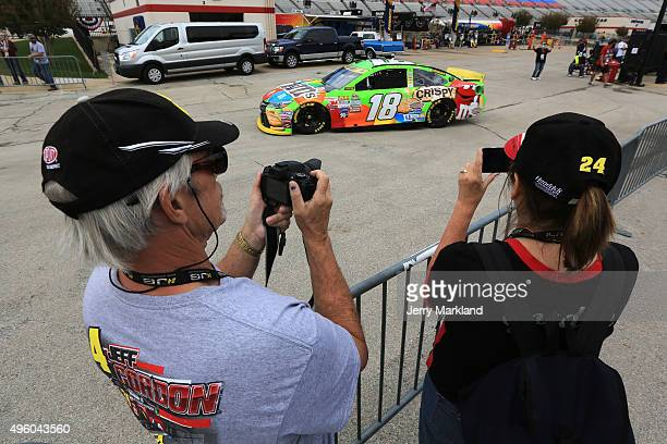 Fans take pictures as Kyle Busch driver of the MM's Crispy Toyota drives through the garage area during practice for the NASCAR Sprint Cup Series AAA...