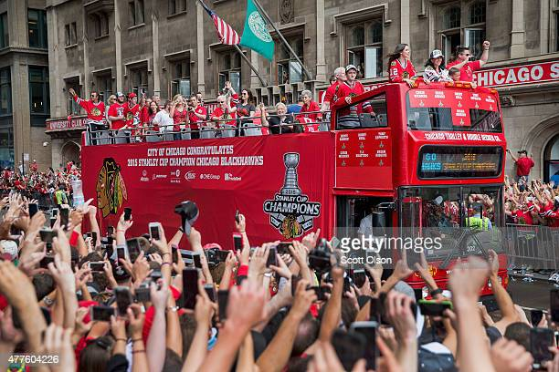 Fans take pictures as members of the Chicago Blackhawks' parade through downtown to celebrate their winning of the Stanley Cup on June 18 2015 in...
