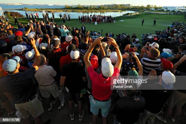 Fans take pictures as US President Donald Trump presents Captain Steve Stricker and the US Team with the trophy after they defeated the International...
