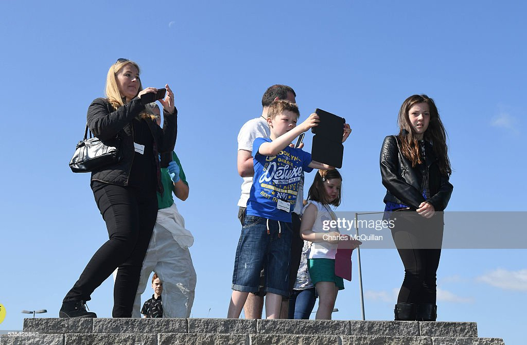 Fans take pictures from vantage points as the Northern Ireland football team make their training camp departure at George Best City Airport on May 30, 2016 in Belfast, Northern Ireland. Northern Ireland have qualified for the Euro 2016 football championship finals in France, the first time the province has qualified for an international football tournament final since 1986.