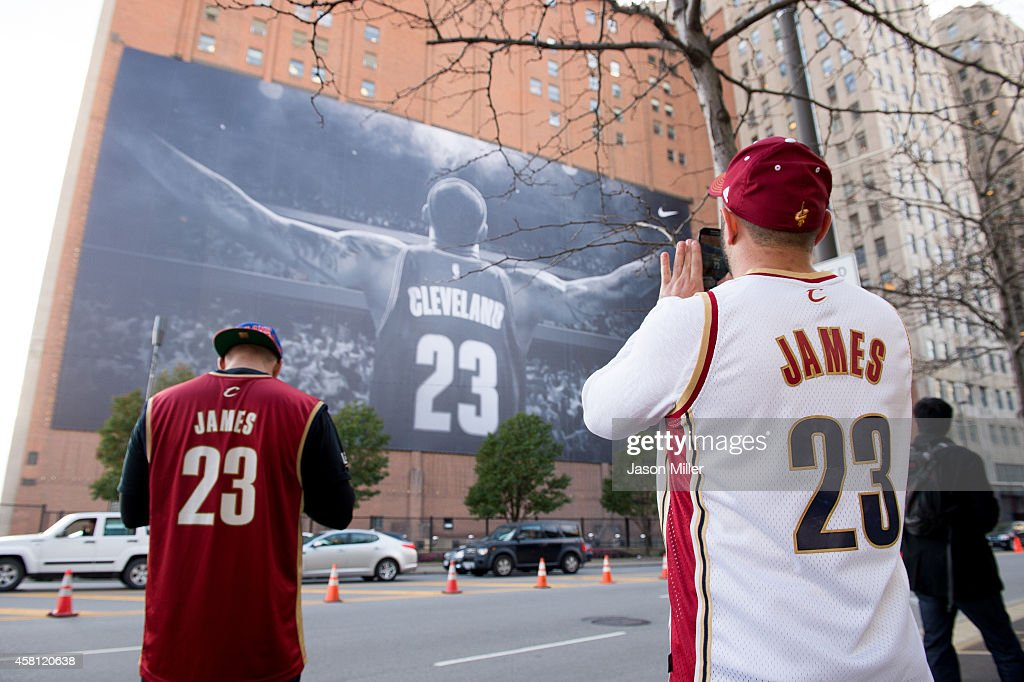 Fans take pictures of a LeBron James #23 of the Cleveland Cavaliers banner outside Quicken Loans Arena before a game against the New York Knicks on October 30, 2014 in Cleveland, Ohio.