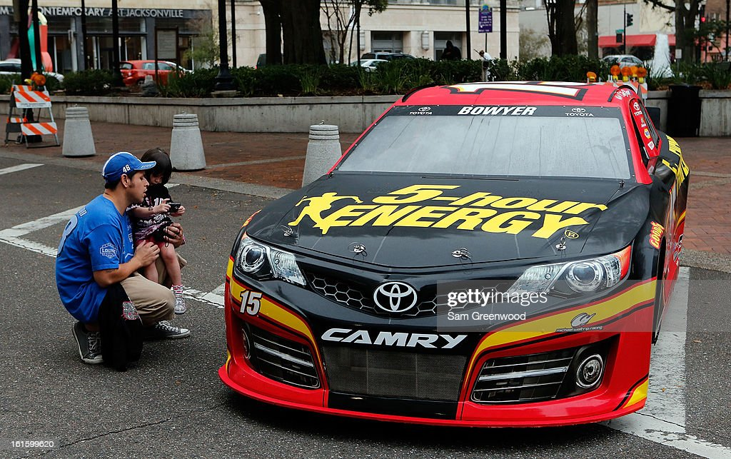 Fans take pictures of the Gen-6 #15 5-hour Energy Toyota driven by Clint Bowyer (not pictured) during the Road to Daytona Fueled By Sunoco Tour stop at City Hall on February 12, 2013 in Jacksonville, Florida.