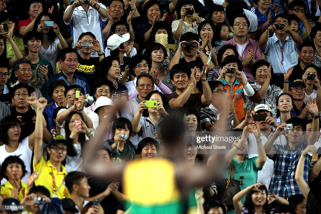 Fans take pictures of Usain Bolt of Jamaica following his victory and a new world record in the men's 4x100 metres relay final during day nine of 13th IAAF World Athletics Championships at Daegu Stadium on September 4, 2011 in Daegu, South Korea.