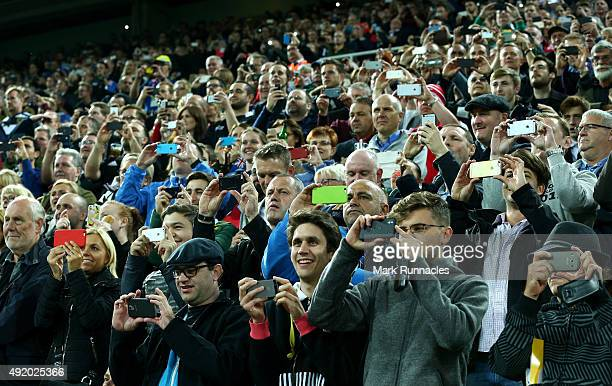 Fans take pictures using their mobile phones during the 2015 Rugby World Cup Pool C match between New Zealand and Tonga at St James' Park on October...