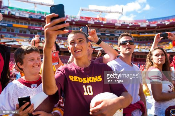 Fans take pictures with their cell phones prior to the game between the Cincinnati Bengals and Washington Redskins at FedEx Field on September 23...
