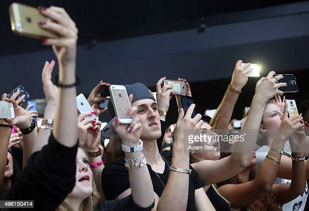Fans take pictures with their mobile phones of Kid Ink stage name of Brian Todd Collins as he performs during a concert at Columbiahalle on November...