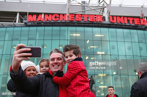 Fans take selfie photographs outside the stadium prior to the Barclays Premier League match between Manchester United and Swansea City at Old...