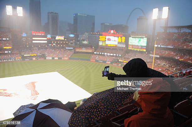 Fans take selfies as they sit during a rain delay prior to a game between the St Louis Cardinals and the Los Angeles Dodgers at Busch Stadium on May...