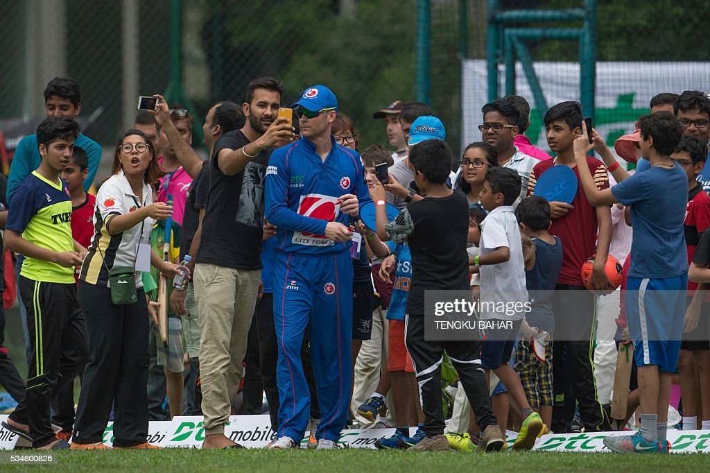Fans take selfies with Michael Clarke of the Kowloon Cantons as he signs autographs for fans in between play against Hung Hom JD Jaguars during the Hong Kong T20 Blitz cricket tournament in Hong Kong on May 28, 2016. Former Australia captain Michael Clarke on May 27 said his body felt 15 years younger after a spell away from cricket as he prepared for a comeback at the Hong Kong T20 Blitz. / AFP / TENGKU