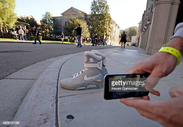 A fans takes a photograph of Nike 'Back to the Future' Air Mag sneakers in the Hill Valley Courthouse square in the back lot of Universal Studios...