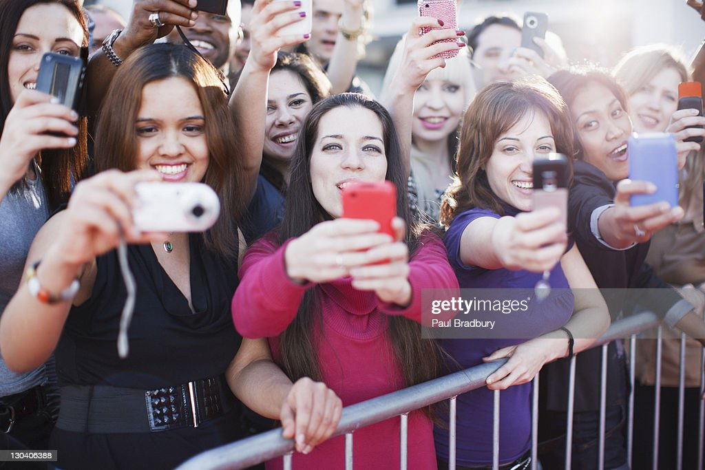 Fans taking pictures with cell phone behind barrier