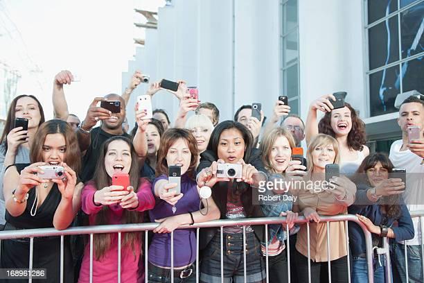 Les Fans de prendre des photos avec téléphone portable derrière barrière