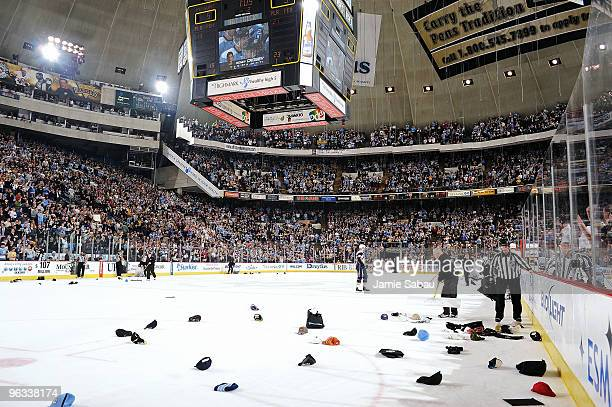 Fans toss their hats on the ice after Sidney Crosby of the Pittsburgh Penguins scores a hat trick in the second period against the Buffalo Sabres on...