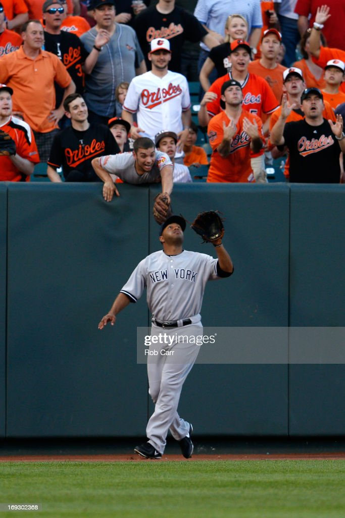 Fans try and distract left fielder <a gi-track='captionPersonalityLinkClicked' href=/galleries/search?phrase=Vernon+Wells&family=editorial&specificpeople=212943 ng-click='$event.stopPropagation()'>Vernon Wells</a> #12 of the New York Yankees as he waits to catch a ball hit by J.J. Hardy #2 of the Baltimore Orioles (not pictured) for the third out of the first inning at Oriole Park at Camden Yards on May 22, 2013 in Baltimore, Maryland.
