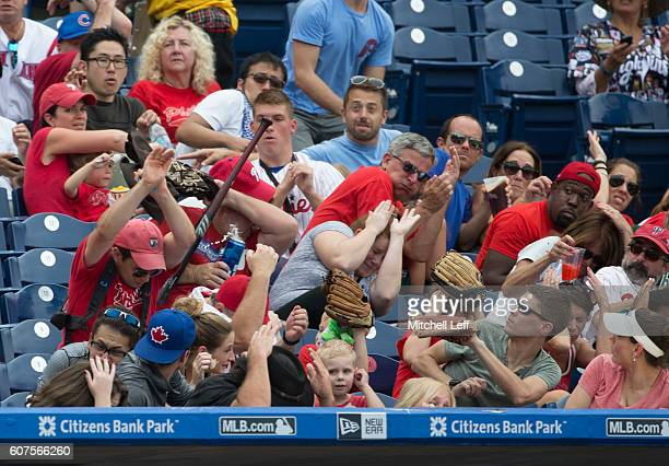 Fans try to avoid getting hit by a baseball bat that Jorge Alfaro of the Philadelphia Phillies lost control of in the bottom of the sixth inning...