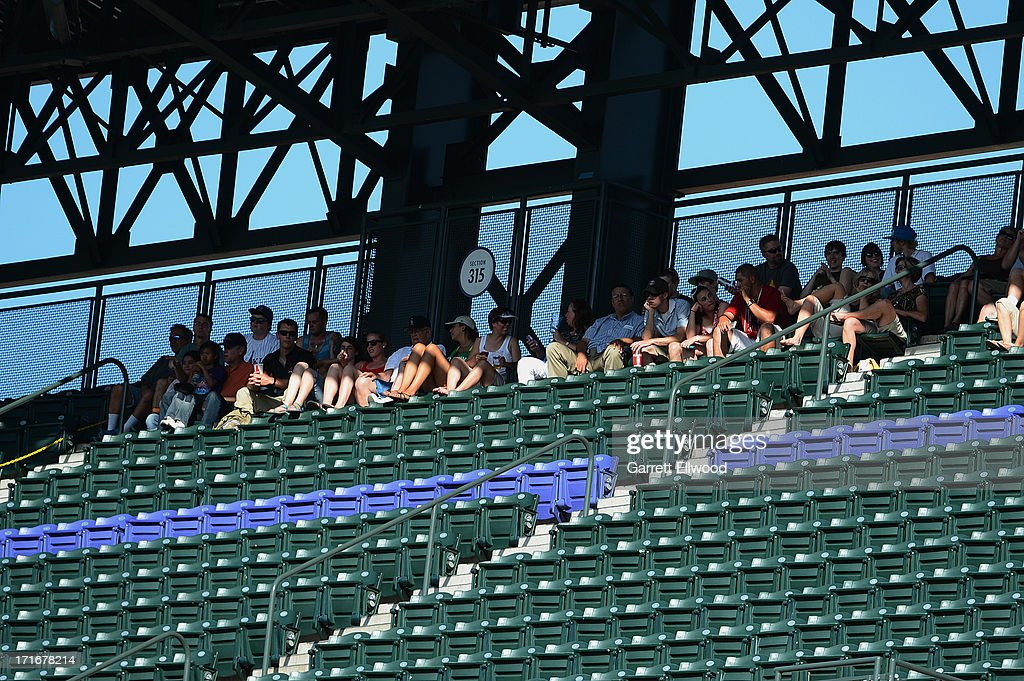 Fans try to avoid the sun and heat during the game between the New York Mets and the Colorado Rockies at Coors Field on June 27, 2013 in Denver, Colorado. Photo by Garrett W. Ellwood/Getty Images)