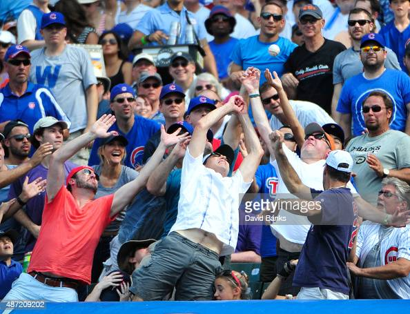 Fans try to catch a foul ball during a game between the Chicago Cubs and the Arizona Diamondbacks on September 6 2015 at Wrigley Field in Chicago...