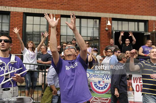 Fans try to catch peanuts thrown into the crowd on Blake Street before the start of the game The Colorado Rockies took on the San Diego Padres on...