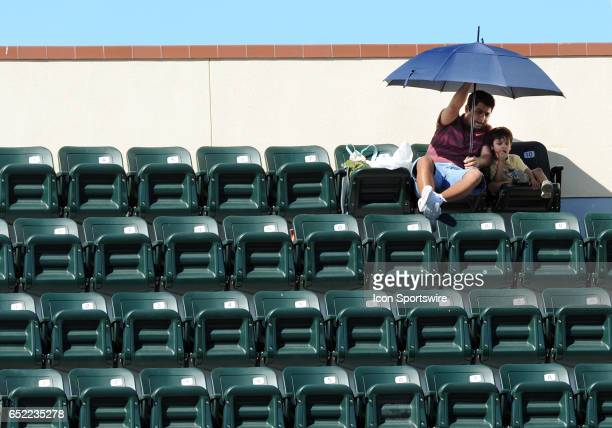 Fans under an umbrella at the top of stadium one watch a match between ATP players Fabio Fognini and JoWilfried Tsonga on March 11 2017 during the...
