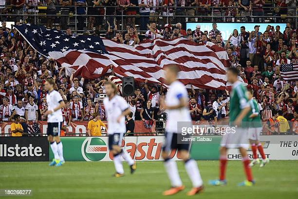 Fans unfurl a large US flag after the US Men's National Team scored their second goal against Mexico in the second half at Columbus Crew Stadium on...