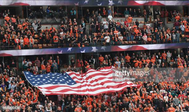 Fans unfurl an American flag during the national anthem before the game between the Anaheim Ducks and the Calgary Flames in Game Two of the Western...