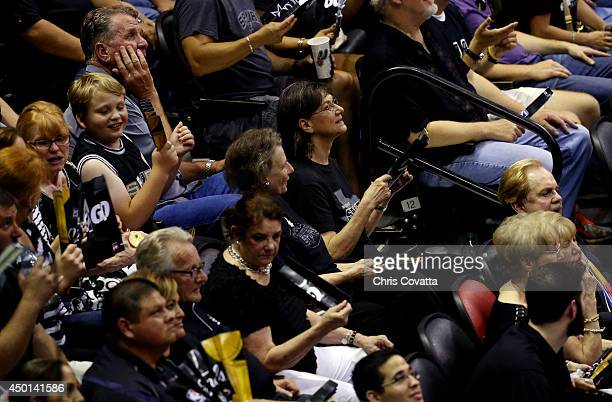 Fans use programs as fans after the air conditioning malfunctioned during Game One of the 2014 NBA Finals between the Miami Heat and the San Antonio...