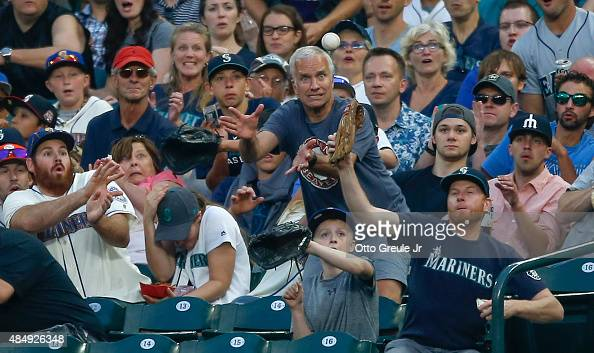 Fans vie for a foul ball off the bat of Austin Jackson of the Seattle Mariners in the sixth inning against the Chicago White Sox at Safeco Field on...