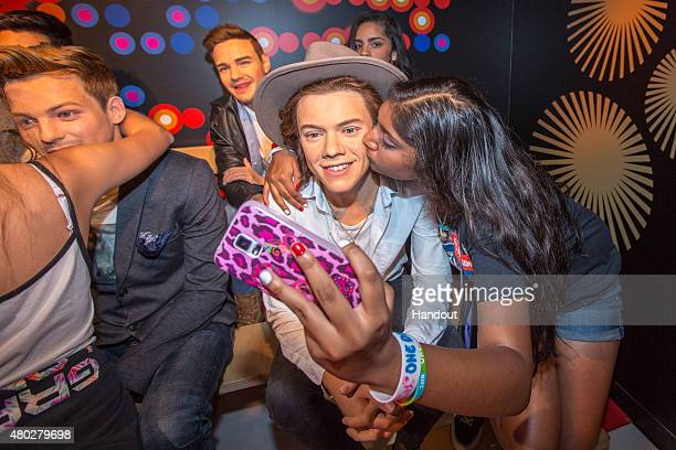 Fans view the wax figures depicting Niall Horan Liam Payne Harry Styles and Louis Tomlinson of One Direction while they are on display at Madame...