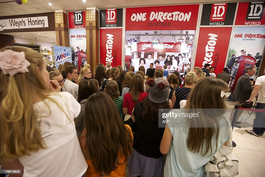 Fans wait for the opening of a temporary store selling merchandising of British-Irish boy band One Direction on August 16, 2013, at the Waasland Shopping Center in Sint-Niklaas. The shopping center issued extra security to receive the band's fans. AFP PHOTO / BELGA / NICOLAS MAETERLINCK