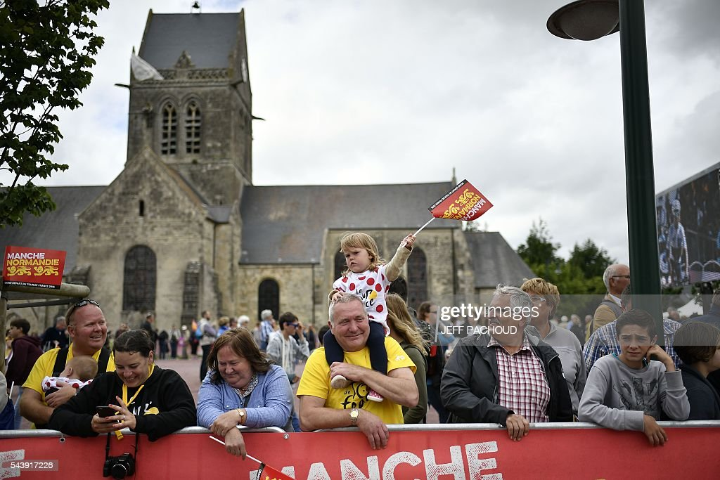 Fans wait for the parade prior to the start of the team presentation ceremony in Sainte-Mere-Eglise on July 30, 2016, two days before the start of the 103rd edition of the Tour de France cycling race. The 2016 Tour de France will start on July 2 in the streets of Le Mont-Saint-Michel and ends on July 24, 2016 down the Champs-Elysees in Paris. / AFP / jeff pachoud