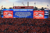 Fans wait in their seats as a weather delay is displayed on the jumbotron prior to the game between the Denver Broncos and the Baltimore Ravens at...