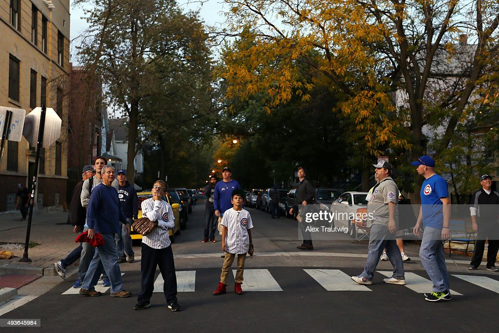 Fans wait on Waveland Avenue for baseballs hit out of the park during batting practice prior to Game 4 of the NLCS between the Chicago Cubs and the...