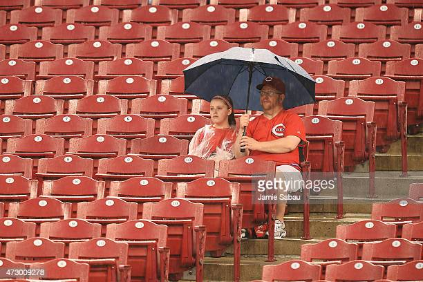 Fans wait out a rain delay to the start of the game between the Cincinnati Reds and the Atlanta Braves at Great American Ball Park on May 11 2015 in...