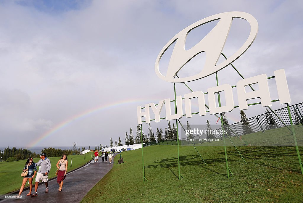 Fans walk alongside a Hyundai sign with a rainbow in the background before the first round of the Hyundai Tournament of Champions at the Plantation Course on January 4, 2013 in Kapalua, Hawaii.
