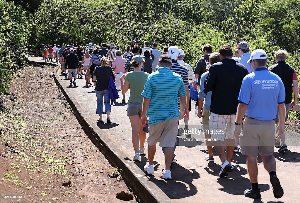Fans walk back to the clubhouse after play was suspended due to high winds during the replay of the first round of the Hyundai Tournament of Champions at the Plantation Course on January 6, 2013 in Kapalua, Hawaii.