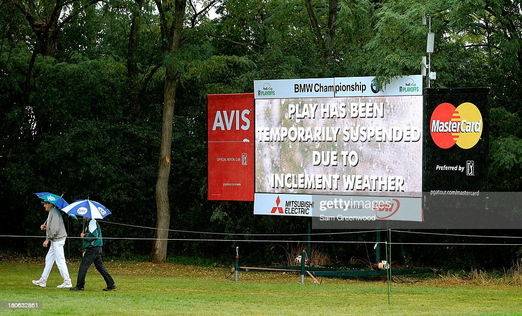 Fans walk by a scoreboard displaying a message that play is suspended due to inclement weather during the Final Round of the BMW Championship at Conway Farms Golf Club on September 15, 2013 in Lake Forest, Illinois.