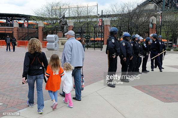 Fans walk by police outside Oriole Park at Camden Yards before the game was postponed between the Baltimore Orioles and the Chicago White Sox on...
