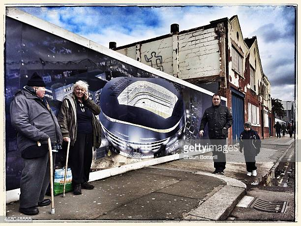 Fans walk past a mural depicting design for a new Tottenham Hotspur stadium before the Barclays Premier League match between Tottenham Hotspur and...