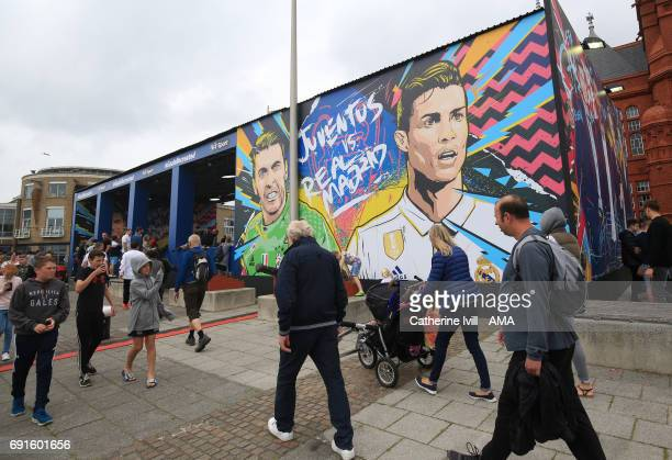 Fans walk past a mural of Gianluigi Buffon of Juventus and Cristiano Ronaldo of Real Madrid prior to the UEFA Champions League Final between Juventus...