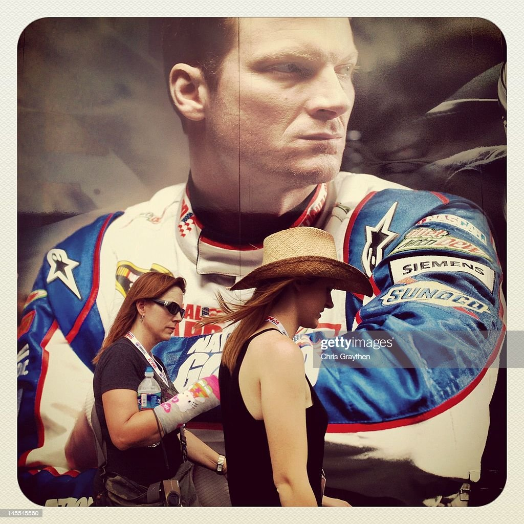 Fans walk past a photo of Dale Earnhardt Jr., driver of the #88 AMP Energy/National Guard Chevrolet prior to the NASCAR Sprint Cup Series Coca-Cola 600 at Charlotte Motor Speedway on May 27, 2012 in Concord, North Carolina.
