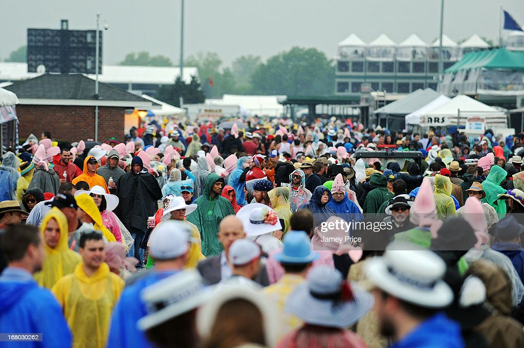 Fans walk through the infield, while it rains, prior to the 139th running of the Kentucky Derby at Churchill Downs on May 4, 2013 in Louisville, Kentucky.