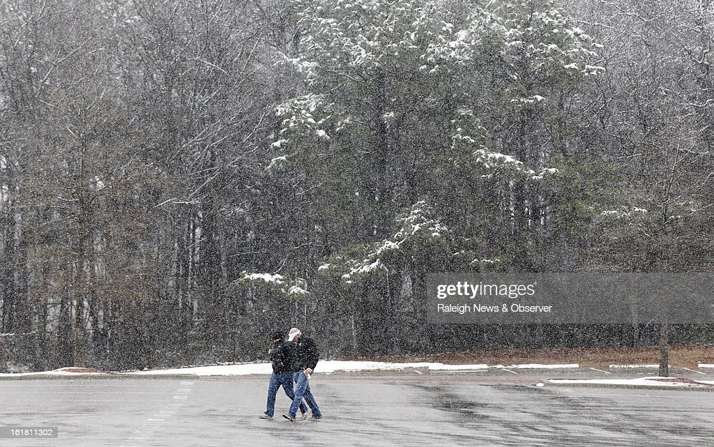 Fans walk to PNC Arena in Raleigh, North Carolina, in the snow before North Carolina State's basketball game against Virginia Tech, Saturday, February 16, 2013.