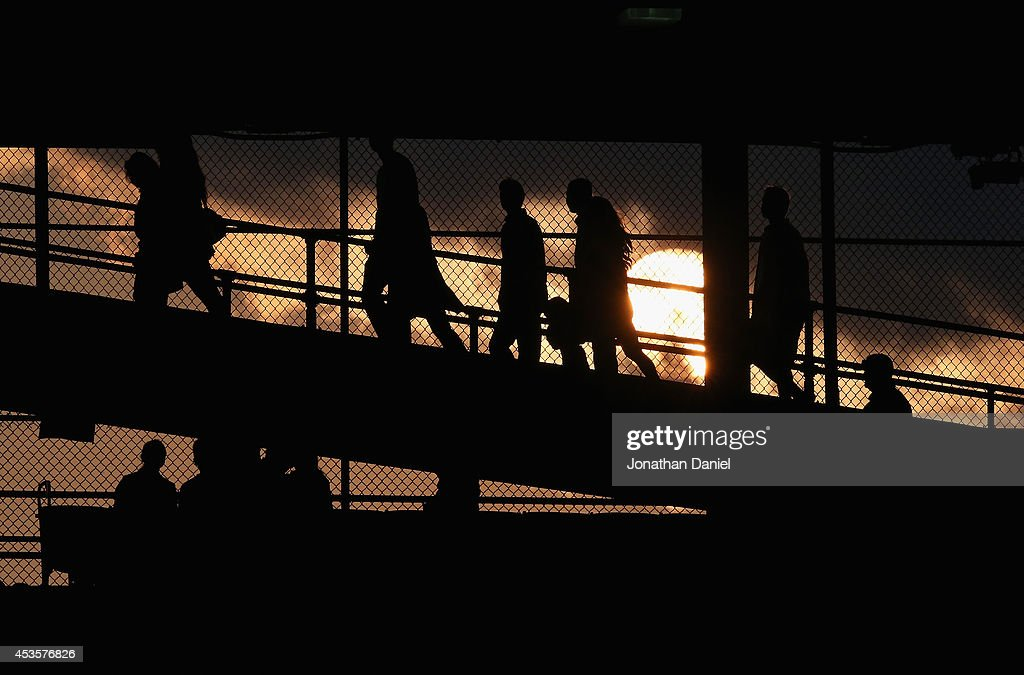Fans walk to their seats at sunset during a game between the Chicago Cubs and the Milwaukee Brewers at Wrigley Field on August 13, 2014 in Chicago, Illinois.