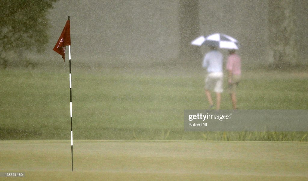 Fans walk under an umbrella in the rain during the final match of the U.S. Amateur Championship on August 17, 2014 at the Atlanta Athletic Club in Johns Creek, Georgia.