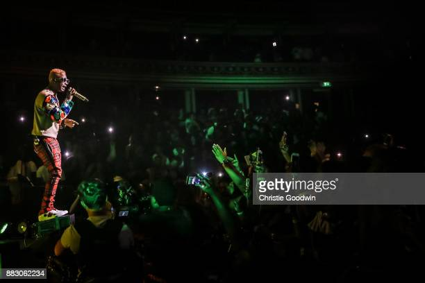 Fans watch and film as Wizkid performs on stage at The Royal Albert Hall on September 29 2017 in London England