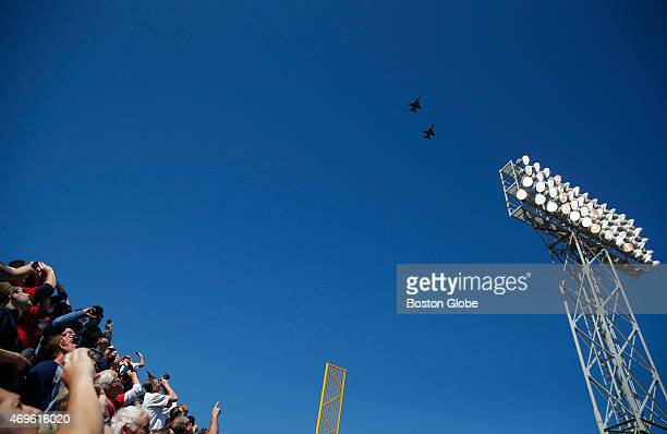 Fans watch and take pictures of a flyover during the Red Sox home opener at Fenway Park in Boston on April 13 2015