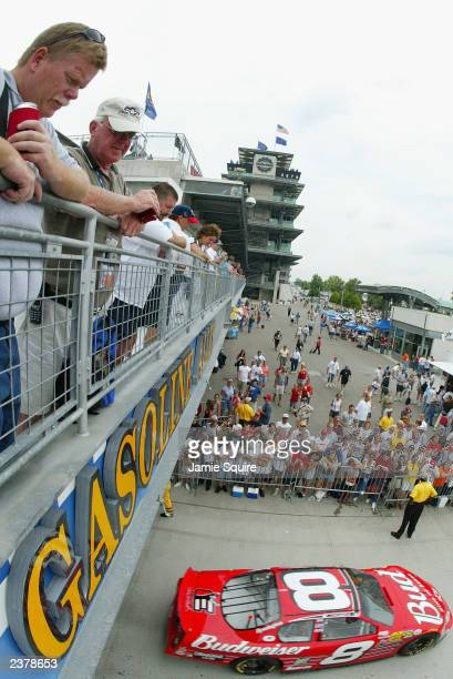 Fans watch as Dale Earnhardt Jr driver of the Budweiser Chevrolet Monte Carlo enters Gasoline Alley during practice for the NASCAR Brickyard 400 on...