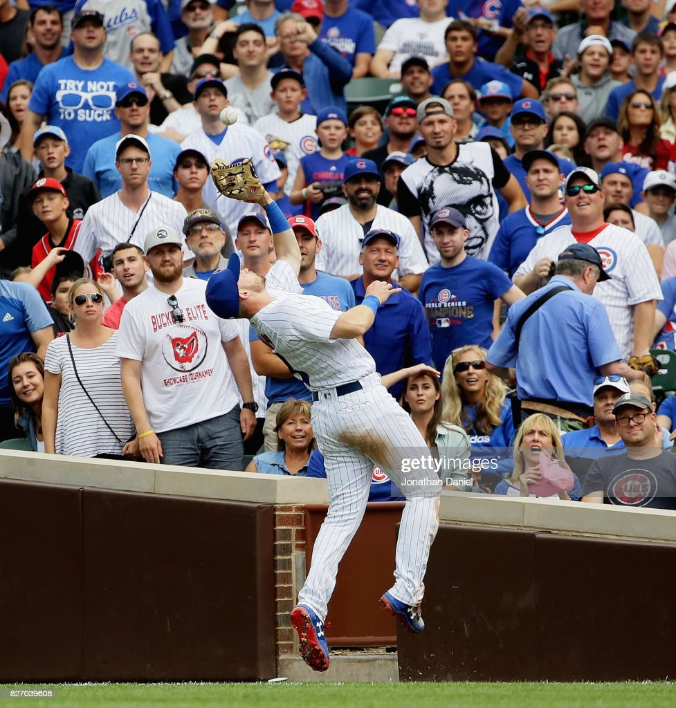 Fans watch as Ian Happ #8 of the Chicago Cubs makes an over-the-shoulder catch of a ball hit by Ryan Zimmerman of the Washington Nationals in the 6th inning at Wrigley Field on August 6, 2017 in Chicago, Illinois.