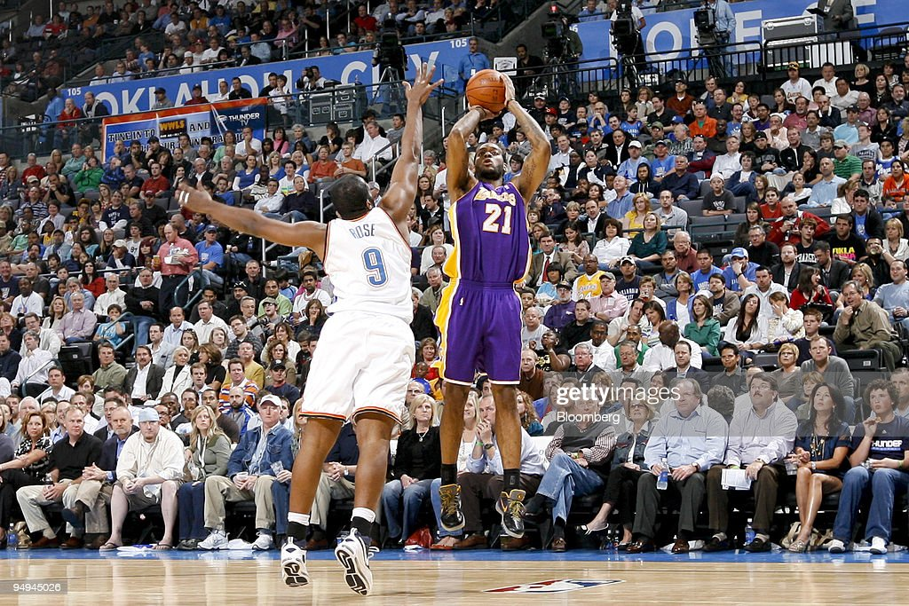 Fans watch as Los Angeles Lakers forward Josh Powell, 21, shoots over Oklahoma City Thunder forward Malik Rose during a National Basketball Association (NBA) game at the Ford Center in Oklahoma City, Oklahoma, U.S., on Tuesday, March 24, 2009. Nearly three decades after an energy bust that forced 122 banks to close statewide, Oklahoma City is in the fifth year of an economic expansion that's produce the lowest jobless rate for a major metro U.S. area. Oklahoma City demonstrated it could support a NBA team, encouraging the Seattle Supersonics to move permanently and become the Thunder, which now draw crowds as large as the Boston Celtics.